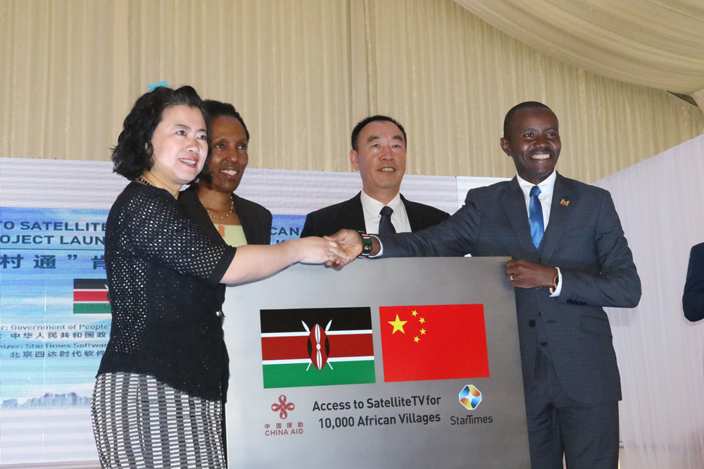 Sun Baohong (front left), China's ambassador to Kenya, shakes hands with Joe Mucheru (front right), Kenya's ICT cabinet secretary, during the launch of a project to bring satellite TV to 800 villages. The launch was held in Nairobi, Kenya on Thursday. Catherine Gitau, secretary of the ICT, and David Zhang, CEO of StarTimes Kenya, look on. [Liu Hongjie/China Daily]