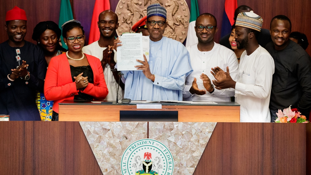 President Buhari in May signed the bill  reducing the age limit to seek political office  [Al Jazeera]