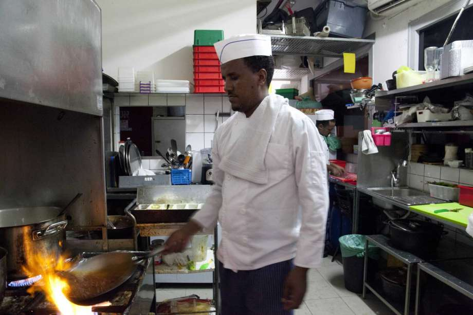 In this Wednesday, Aug. 8, 2018 photo, Eritrean migrant Russom Weldu Weldeslasie works at a restaurant in Tel Aviv, Israel. African migrants coming into Israel have been detained, threatened with deportation and faced hostility from lawmakers and residents. Now, they face another burden: a de facto 20 percent salary cut that has squeezed them financially and driven them further into poverty.
