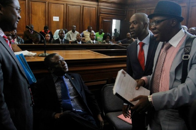 President Mnangagwa (seated) says he has reached out to Chamisa (standing) to call for calm after violence erupted in Harare in a tense build up to the release of election results expected to be won by the ruling ZANU PF