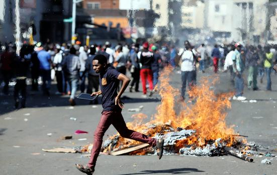 RUNNING FOR COVER: Nelson Chamisa's MDC supporters barricade a road in Harare . Picture: Siphiwe Sibeko/Reuters