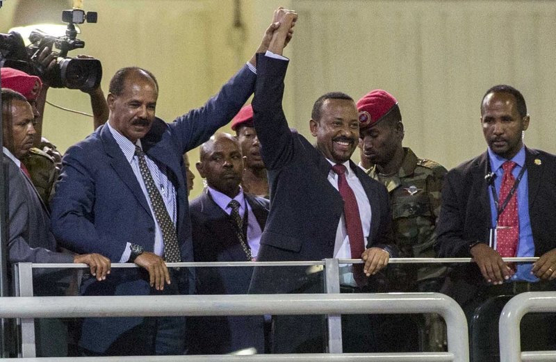 Eritrean President Isaias Afwerki, second left, and Ethiopia's Prime Minister Abiy Ahmed, center, hold hands as they wave at the crowds in Addis Ababa, Ethiopia, Sunday July 15, 2018. Official rivals just weeks ago, the leaders of Ethiopia and Eritrea have embraced warmly to the roar of a crowd of thousands at a concert celebrating the end of a long state of war. A visibly moved Eritrean President Isaias Afwerki, clasping his hands over his heart, addressed the crowd in Ethiopia's official language, Amharic, on his first visit to the country in 22 years. (AP Photo/Mulugeta Ayene)