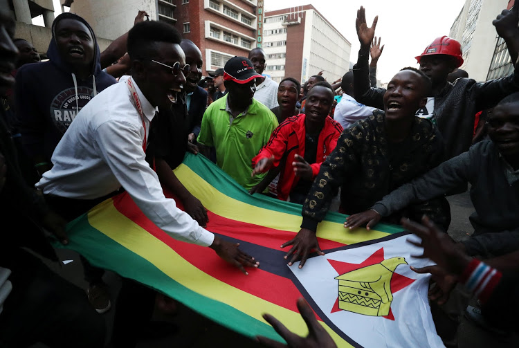 Supporters of the opposition Movement for Democratic Change party of Nelson Chamisa sing and dance in the street outside the party's headquarters following general elections in Harare, Zimbabwe, July 31, 2018.REUTERS/Mike Hutchings