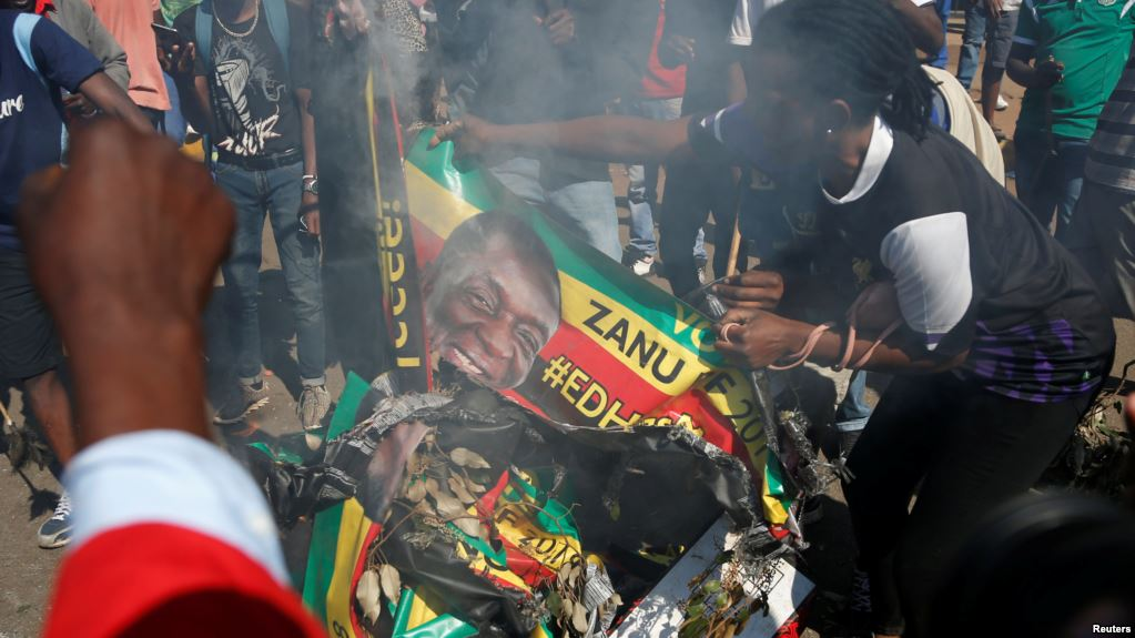 Supporters of the opposition Movement for Democratic Change party (MDC) of Nelson Chamisa burn an election banner with the face of Zimbabwe's President Emmerson Mnangagwa in Harare, Zimbabwe, Aug. 1, 2018.