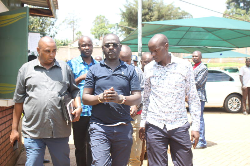 Migori Governor Okoth Obado's aide Caspal Obiero (in handcuffs) and Obado's bodyguard Elvis Omondi (behind) are led to Kisii law court on September 19, 2018. [Sammy Omingo/Standard]