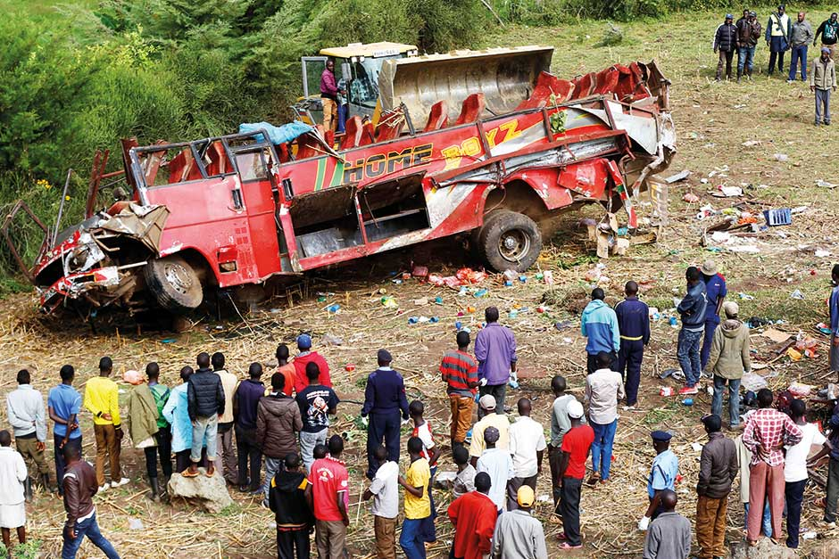 Residents look at the wreckage of a bus that crashed, near Fort Ternan along the Londiani-Muhoroni road in Kericho county, Kenya.
