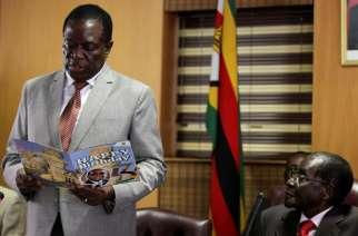 FILE PHOTO: Zimbabwe's President Robert Mugabe looks on as his deputy Emmerson Mnangagwa reads a card during Mugabe's 93rd birthday celebrations in Harare, Zimbabwe, February 21, 2017. REUTERS/Philimon Bulawayo/File Photo