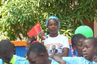 A woman carrying the flag of China dressed with a T-shirt with the face of the mozambican president Filipe Nyusi. © Alexandre Nhampossa / PanAfricanVisions
