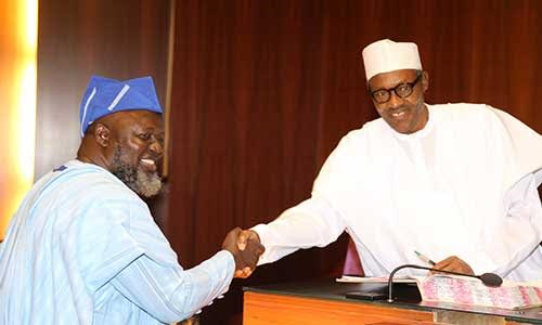President Muhammadu Buhari in handshake with his Minister of Communications, Barrister Abdul-Raheem Adebayo Shittu