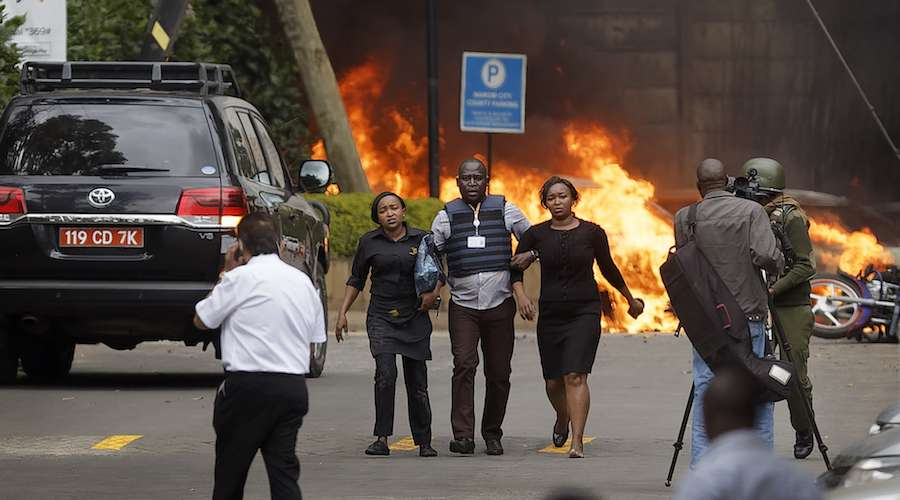 "Security forces help civilians flee the scene as cars burn behind, at a hotel complex in Nairobi, Kenya Tuesday, Jan. 15, 2019. Extremists have launched an attack on a luxury hotel in Kenya's capital, sending people fleeing in panic as explosions and heavy gunfire reverberate through the neighborhood. A police officer says he saw bodies, ""but there was no time to count the dead."" Al-Shabab _ the Somalia-based extremist group _ is claiming responsibility. (AP Photo/Ben Curtis)"