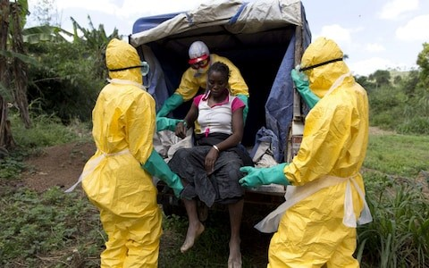 Health workers take a patient to a treatment centre during the 2014 Ebola epidemic in Liberia CREDIT: KENZO TRIBOUILLARD/AFP PHOTO