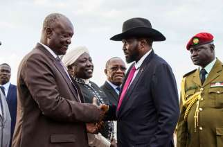 South Sudan's President Salva Kiir (2R) and Minster of Defence Kuol Manyang Juuk (2L) shake hands as Kiir arrives from Sudan's capital Khartoum at Juba Internal Airport in Juba, South Sudan, on June 27, 2018. (Akuot Chol/AFP/Getty Images)