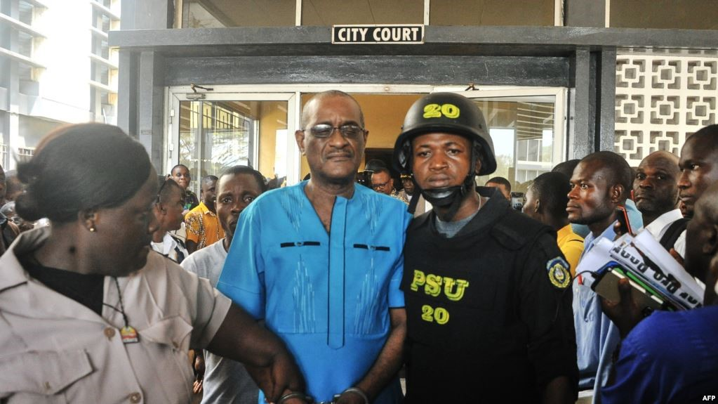 Former deputy governor of the Central Bank of Liberia Charles Sirleaf (C), the son of LIberia's former president Ellen Johnson Sirleaf, is escorted outside the City Court of Monrovia on March 4, 2019, where he appeared in court and charged with economic sabotage.