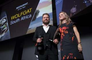 Chef Kobus van der Merwe (L) receives the best Restaurant of the year award for his restaurant 'Wolfgat' in South Africa during the inaugural World Restaurant Awards on February 18, 2019 at the Palais Brongniart in Paris. (Photo credits: AFP/Thomas Samson)