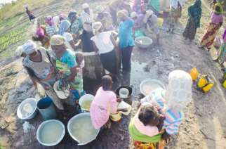 Women work together to collect water from a well for their community in northern Ghana. USAID/ Jennifer Yost